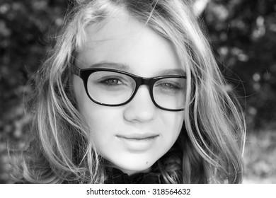 Beautiful blond Caucasian teenage girl in glasses, outdoor monochrome portrait