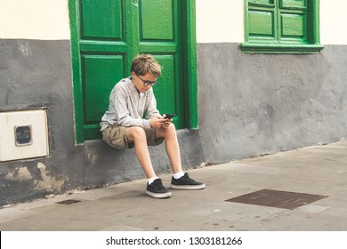 Beautiful blond child with black round eyeglasses sitting on green door step near window looks at the mobile phone chatting with friends street sidewalk rest break write messages share photos read new