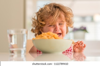 Beautiful blond child eating spaghetti with hands crying with tantrum at home.