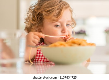 Beautiful blond child eating spaghetti with hands at home