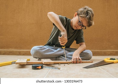 Beautiful blond child works outdoors with carpenter's tools is screwing with a screwdriver on a wooden board carpenter tools yellow saw constructs repairs educational games roller blind meter screws