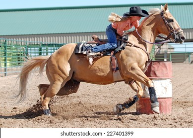 Beautiful blond cowgirl riding a palomino horse in a barrel race at a rodeo.
