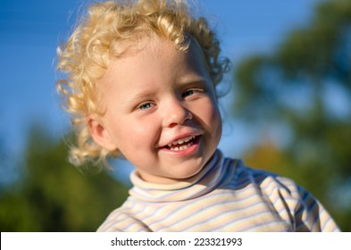Beautiful blond curly boy laughing