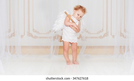 Beautiful blond curly toddler in a while lace dress with wings as a Cupid playing with his flute in the white room with gold moldings in baroque style. Saint Valentines Day celebration