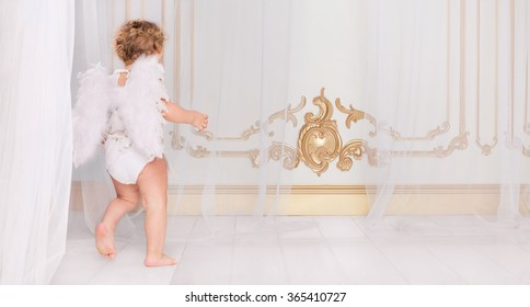 Beautiful blond curly toddler in a while lace dress with wings as a Cupid playing with his flute in the white room in baroque style. Saint Valentines Day