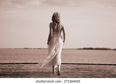 Beautiful blond curly woman wearing evening peach color gown running on a deck at lake. Sepia effect.