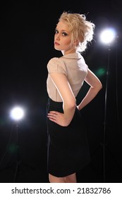 Beautiful blond fashion model posing in studio with backlights