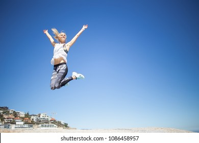 Beautiful blond female fitness model jumping from one rock to another on a bright sunny day