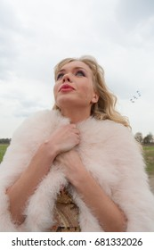 Beautiful blond female model in a beige dress and a short pink fur coat with tears on her face in early spring day on the countryside road