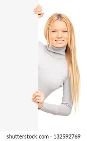 A beautiful blond female posing behind blank panel isolated on white background