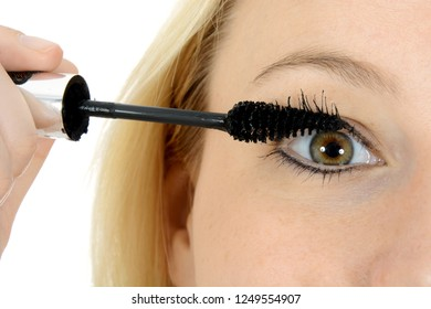 Beautiful blond girl is applying mascara and eyeliner for eye in close up