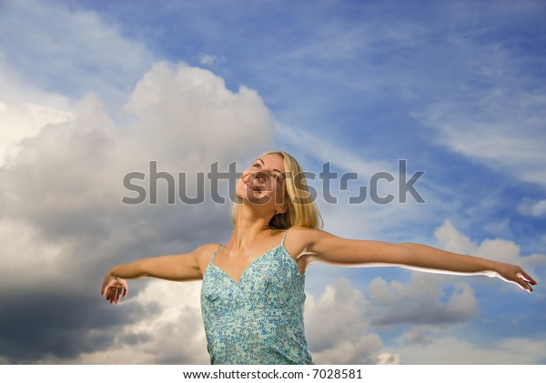 Beautiful blond girl with arms wide open over blue cloudy sky