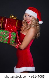 beautiful blond girl in christmas costume with gifts