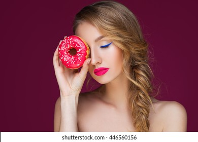 Beautiful blond girl with colorful doughnut