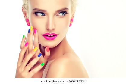 beautiful blond girl with colorful manicure nails .Crimson lips and earrings. Cosmetics,makeup and beauty