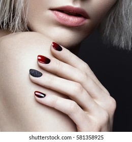 Beautiful blond girl with dark smokey makeup and art manicure design nails. beauty face. Close up. Photos shot in studio