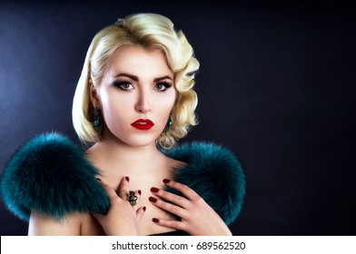 Beautiful blond girl with fur on shoulders posing