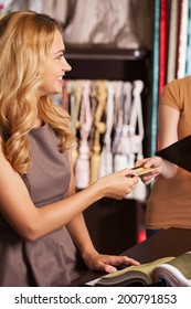 beautiful blond girl giving credit card. attractive woman standing in store and smiling