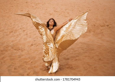 A beautiful blond girl in a golden with brilliant dress with wings, suit is dancing an oriental, East dance in the desert on the sand. Beautiful exotic woman dancer in a costume for belly dancing.