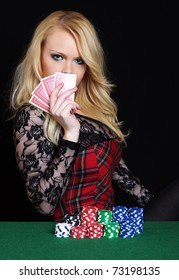 Beautiful blond girl hides behind poker cards