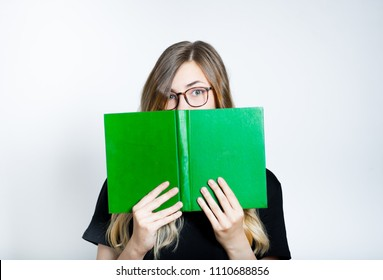 beautiful blond girl hiding behind a book, glasses, isolated studio photo on a background