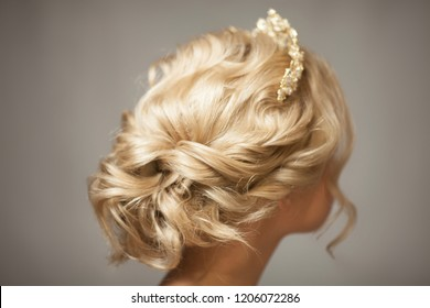 Beautiful blond girl in the image of a bride with a tiara in her hair.