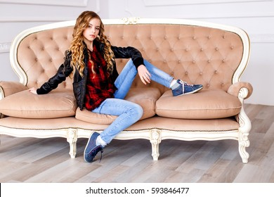 Beautiful blond girl  in jeans and black leather jacket sitting on luxury sofa