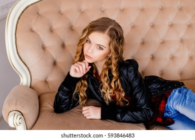 Beautiful blond girl  in jeans and black leather jacket lying on luxury sofa