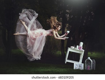 A beautiful blond girl is leaning with a mug of tea over a table. Lack of gravity. Like Alice in Wonderland. A girl with long hair flies like in a fairy tale. Creative colors. Artistic processing.