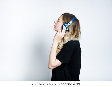 beautiful blond girl listening to music in big headphones, isolated studio photo on background