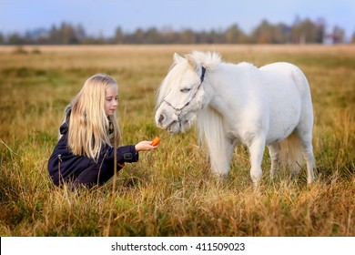 beautiful blond girl with long hair feeding white miniature horse in field carrots