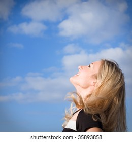 beautiful blond girl looking up to a blue cloudy sky
