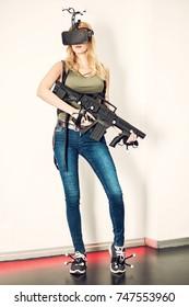 Beautiful blond girl model - virtual reality game player - wearing headset and holding gun