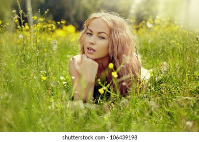 beautiful blond girl on green field with flowers. Rural scene