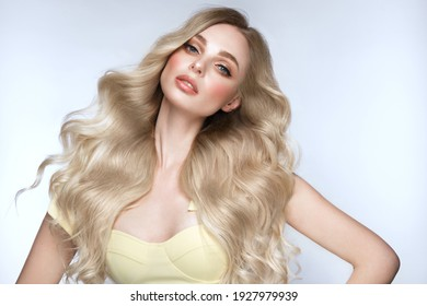 Beautiful blond girl with a perfectly curls hair, and classic make-up. Beauty face and hair. Picture taken in the studio.