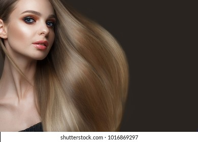 Beautiful blond girl with a perfectly smooth hair, classic make-up and red lips. Beauty face. Picture taken in the studio on a white background.
