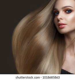 Beautiful blond girl with a perfectly smooth hair, classic make-up. Beauty face. Picture taken in the studio on a white background.