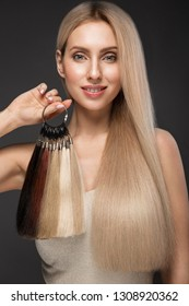 Beautiful blond girl with a perfectly smooth hair, classic make-up with a palette for hair extensions in the hands. Beauty face. Picture taken in the studio.