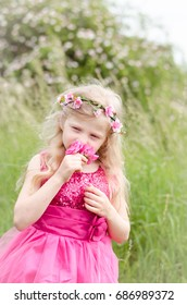 beautiful blond girl in pink dress holding pink rose flower