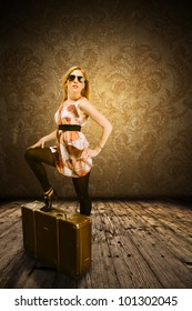 Beautiful blond girl posing on suitcase, in retro design