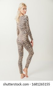Beautiful blond girl posing in studio in leopard dress.