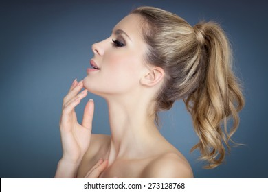 Beautiful blond girl profile with pony tail over blue background.