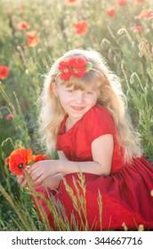beautiful blond girl in red corn poppy field