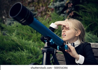 Beautiful blond girl in a school uniform in the park looking through a telescope