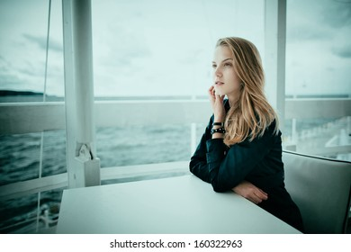 Beautiful blond girl sits in caffee at table