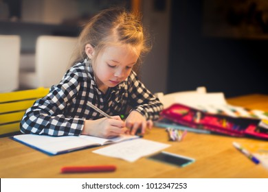 beautiful, blond girl is sitting at the table and is doing schoolwork at home