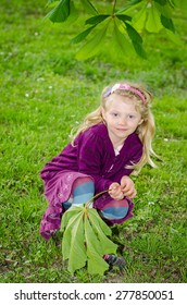 beautiful blond girl squating down in green meadow