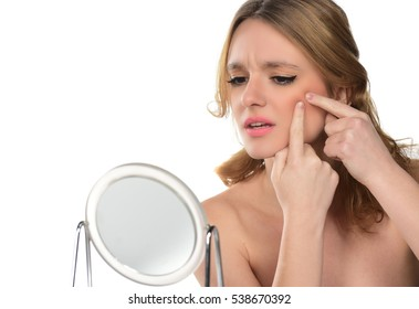 beautiful blond girl squeezes her acne in front of the mirror isolated
