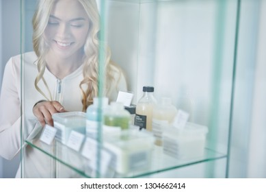 Beautiful blond girl standing behind glass showcase and pointing at cream for skin. She looking at beauty products and smiling