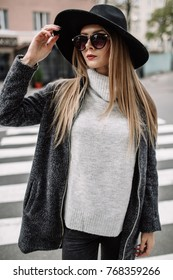 Beautiful blond girl with sunglasses. A model in a stylish wide-brimmed hat at a pedestrian crossing. Harmoniously similar clothes in gray tones. Street style shooting. Women's fashion.